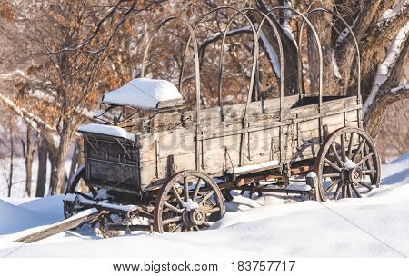 Antique wagon or carriage in snowy landscape.