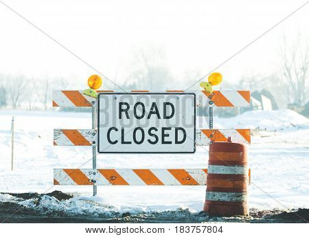 Road Closed sign on blockade in a construction zone in winter.