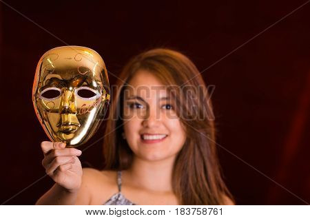 Happy beautiful woman holding a gold mask.