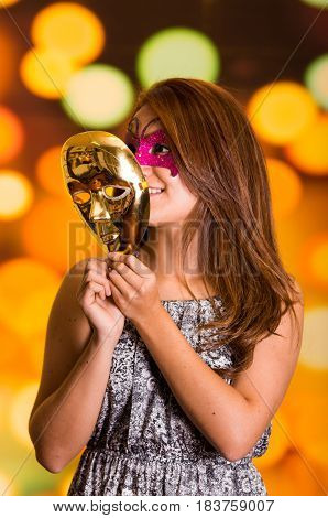 Beauty model woman wearing pink carnival mask with a gold mask in her hands.