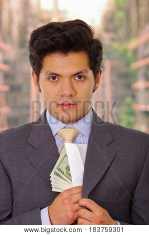 Businessman in dark suit and with tie putting money in his suit.