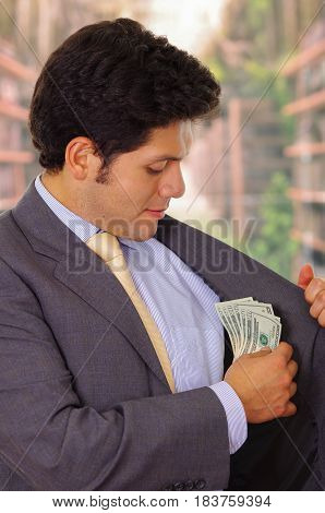 Businessman in dark suit and with tie putting money in his pocket.