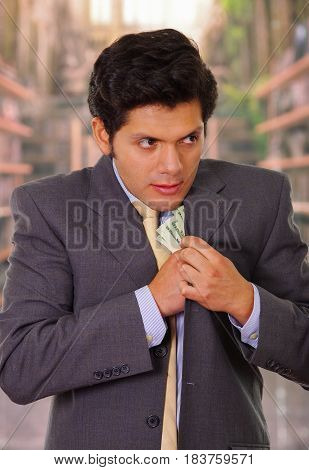 young businessman putting money in his suit.