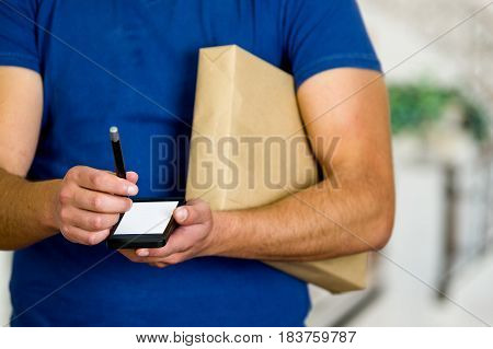 Customer Signing For Delivery From muscle Courier with blue uniform.