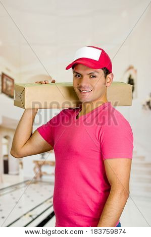 Delivery man in pink uniform holding one box over his shoulders.