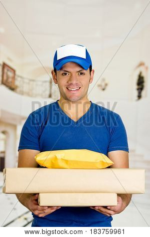 Delivery man in blue uniform holding boxes and documents.