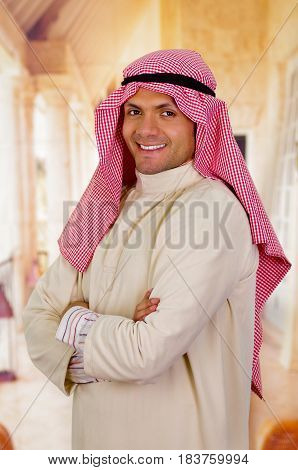 smiling cute arabian man with arms crossed.