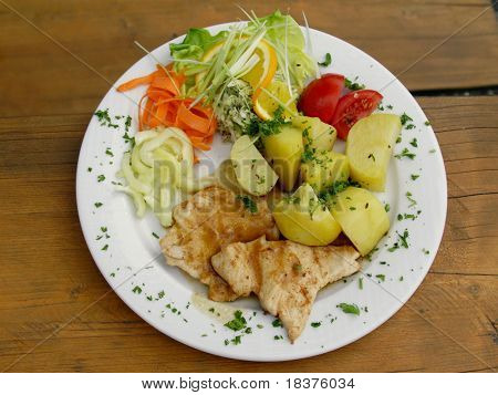 chicken steak with boiled potatoes and vegetables on white plate