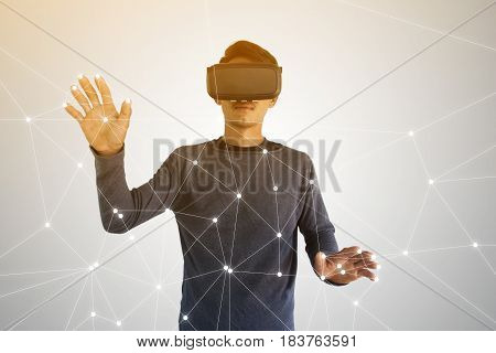 Young businessman wearing virtual reality glasses and touching futuristic network