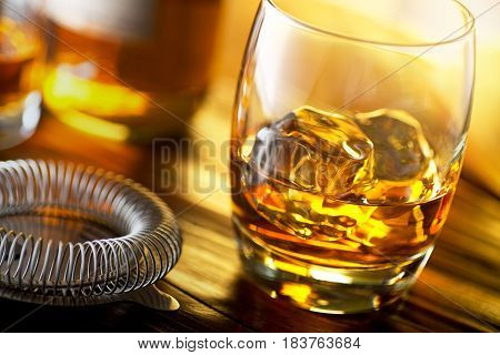 A glass of scotch whiskey with ice on a bar top.