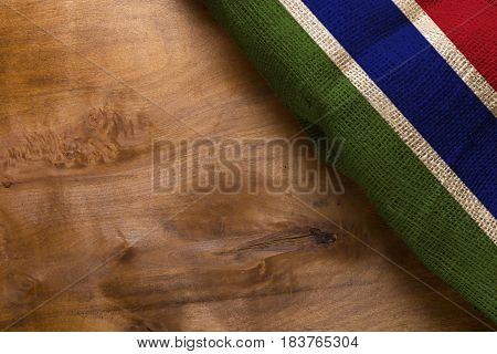 National flag of the country Gambia on a wooden background.