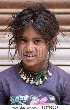 LEH INDIA - JUNE 29 2015: Unknown poor girl begs for money from a passerby on the street in Leh Ladakh. Poverty is a major issue in India