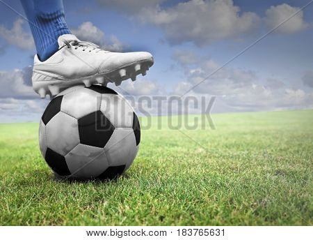 Soccer player with his foot on the ball in a green field