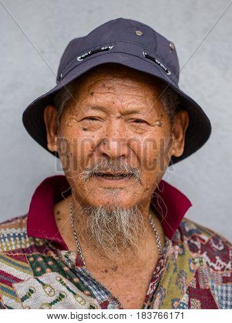 POKHARA NEPAL - SEPTEMBER 28 2016 : Portrait old men in traditional dress in street Pokhara Nepal