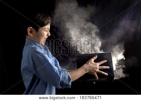 A young boy slams a book with powder in it in this conceptual image.