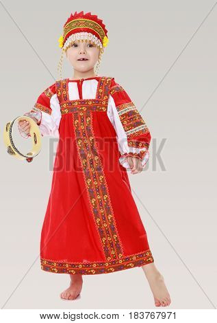 Cheerful little girl in Russian folk dress. The girl hits the drum.