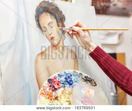 Artist at work. The girl draws a portrait with oil paints in an art school. Courses of drawing for adults.