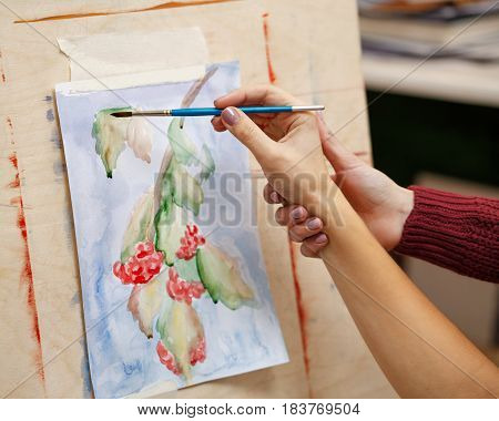 Girl paints still life in watercolor art school. Teacher helps to correct defects in the film. Hands close-up. Courses of drawing for adults.