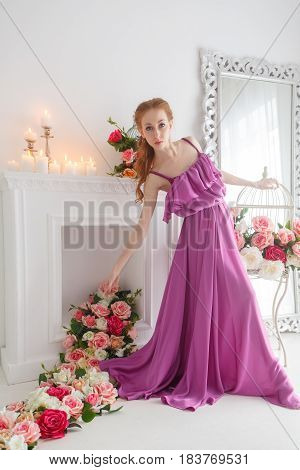 Lovely girl in beautiful dress posing in studio. Spring flowers and a romantic mood.