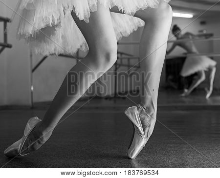Ballerina in pointe shoes and a pack stands on the fingers of the machine. Reflection in the mirror in the ballet class. Classical ballet. Prima ballerina. Shooting close-up. Black and white photography