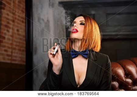 Young attractive girl in a jacket and bow tie smokes electronic cigarette. Femme fatale. Evening makeup smokey eye.
