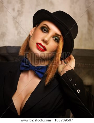 Young attractive girl in a jacket bow tie and bowler hat. Femme fatale. Evening makeup smokey eye.