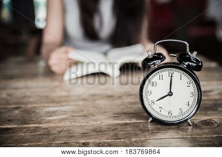 Reading Times, Clock At 8 O'clock On Wood Table With Women Read A Book Blur Background.