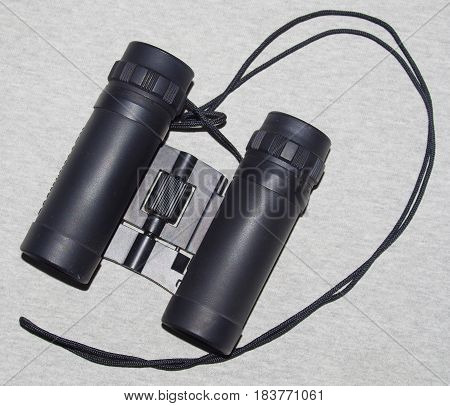 Small pair of black binoculars with a neck strap.