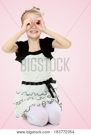 Beautiful little blonde girl dressed in a white short dress with black sleeves and a black belt.The girl folded her palms into a tube in the form of binoculars.Pale pink gradient background.