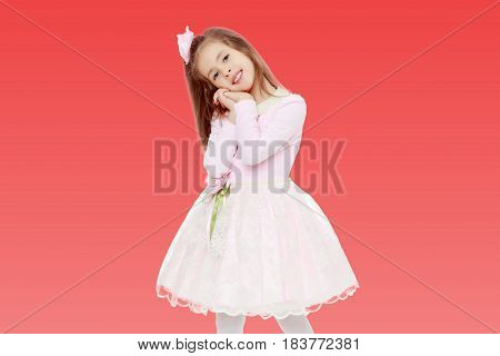 Dressy little girl long blonde hair, beautiful pink dress and a rose in her hair.She holds his palm near his face.