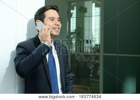 Business man talking smart phone with happy smiling face standing in front of meeting room inside office building background businessman on smart phone online conferance concept