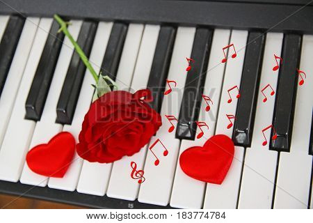 Random musical notes scattered on piano keyboard with red rose between two hearts