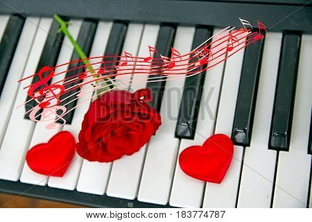 Piano keyboard with rose, two hearts and a musical staff floating above