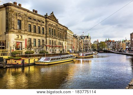 AMSTERDAM, NETHERLANDS - MARCH 30, 2017 Tour Boats Reflection Main Canal Shops Tourists Amsterdam Holland Netherlands. Canals in Amsterdam create beautiful abstract reflections.