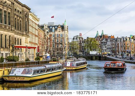 AMSTERDAM, NETHERLANDS - MARCH 30, 2017 Tour Boats Reflection Canal Amsterdam Holland Netherlands. Canals in Amsterdam create beautiful abstract reflections.