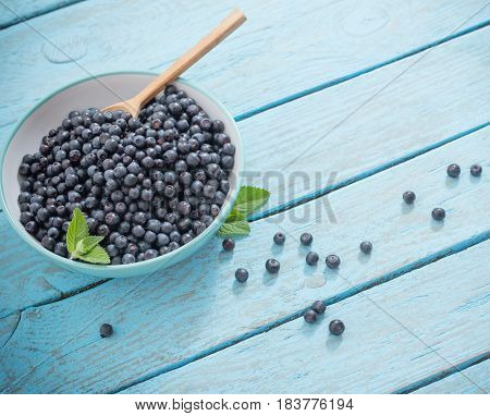 blueberries in plate on a blue wooden table