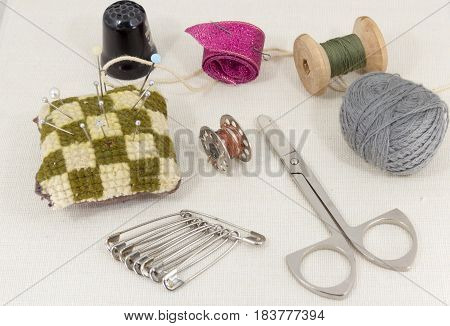 Textile fabric for sewing, accessories for needlework on new textile background. Spool of thread, scissors, thimble, tapemeasure , sewing supplies. Set for needlework top view