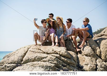 Cheerful friends taking selfie while sitting on rock formations at beach during sunny day