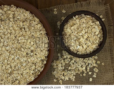 Dry oat flakes oatmeal in bowls on the background