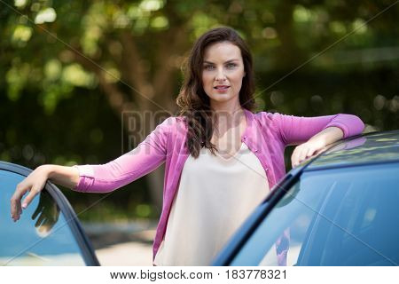 Portrait of confident woman standing by car