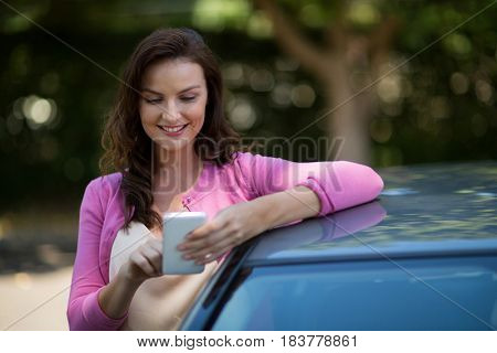 Smiling woman using mobile phone while standing by car
