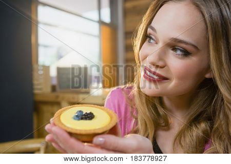 Thoughtful woman holding cupcake in café