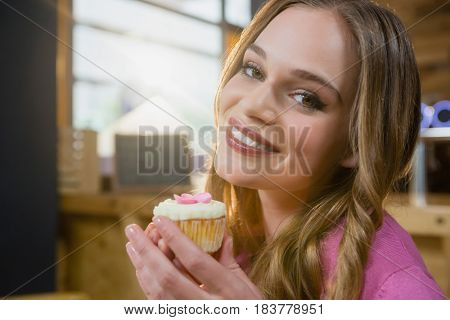 Portrait of beautiful woman holding cupcake in café
