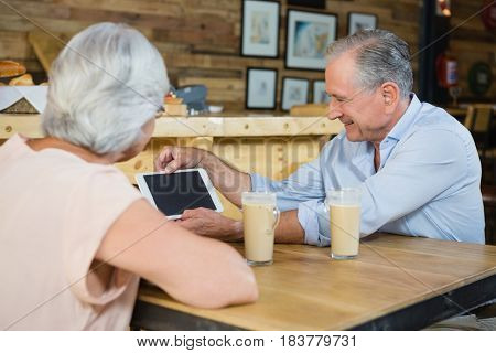 Senior couple using digital tablet while having coffee in cafe