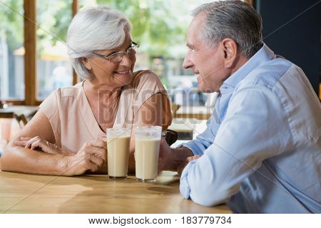 Happy senior couple interacting while having coffee in cafe