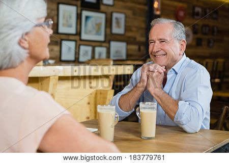 Senior couple interacting while having coffee in cafe