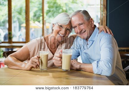 Portrait of happy senior couple having cold coffee in cafe