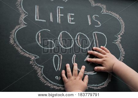 The inscription of life is good and white chalk on a dark griffeyev background in a frame and small children's palms