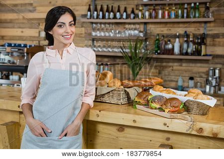 Portrait of waitress leaning at counter in cafe