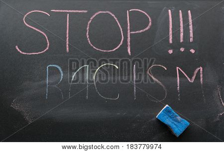 The inscription of the stop racism with a chalk on the slate and the sponge with which the inscription is slightly erased